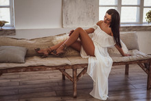 Beautiful Tanned Woman Lying On The Bed In A White Dress.
