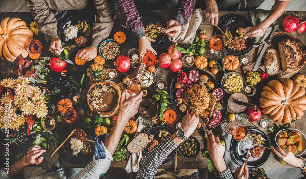 Fototapety, obrazy: Family celebrating Thanksgiving day. Flat-lay of eating and pouring wine peoples hands over Friendsgiving table with traditional Fall food, roasted turkey, candles, pumpkin pie, top view
