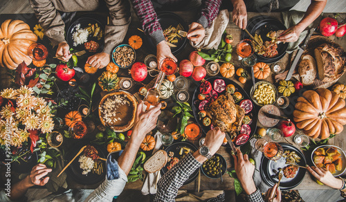 obraz PCV Family celebrating Thanksgiving day. Flat-lay of eating and pouring wine peoples hands over Friendsgiving table with traditional Fall food, roasted turkey, candles, pumpkin pie, top view