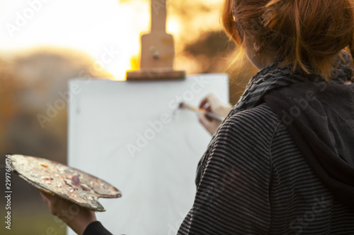 back head of red-haired girl with a bun painting a picture on an easel in nature Canvas Print
