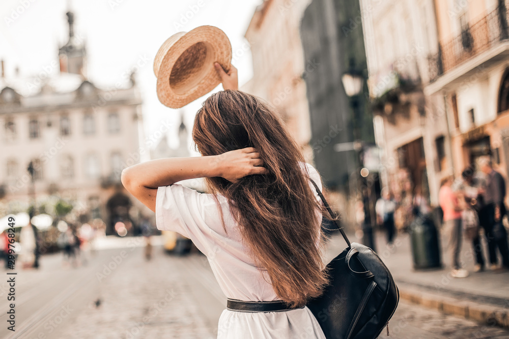 Fototapety, obrazy: Young stylish woman walking on the old town street, travel with backpack, straw hat, wearing trendy outfit.