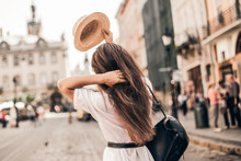 Young Stylish Woman Walking On The Old Town Street, Travel With Backpack, Straw Hat, Wearing Trendy Outfit.