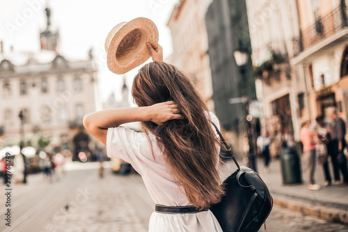 obraz lub plakat Young stylish woman walking on the old town street, travel with backpack, straw hat, wearing trendy outfit.