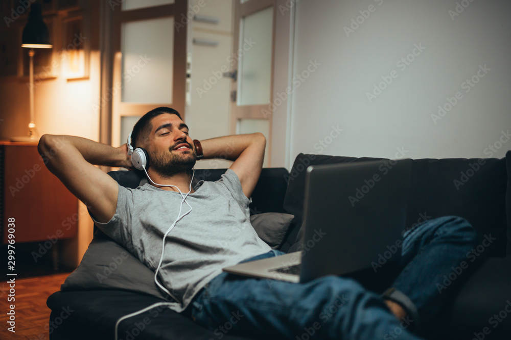 Fototapeta man relaxing in his apartment listening to a music