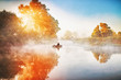 Fisherman in rubber boat making fish-rod fishing on river during sunrise with amazing sun light. Beautiful autumnal scene, colorful yellow trees along river banks. Riverside during fall season.