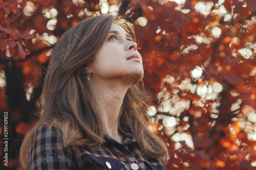 profile of a beautiful young woman looking up gratefully, girl walking through autumn nature in a park