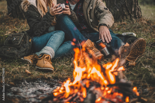 Traveler couple camping in the forest and relaxing near campfire after a hard day Fototapete