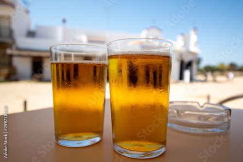 Cold amber color light spanish beer served in glass in outdoor cafe in town on s Wallpaper Mural