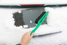 Man Cleaning Car From Snow With Brush. Snow-covered Car Windshield. Parked Car Covered With Snow During Snowing In Winter Time.