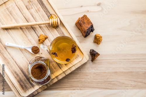 Flat lay view wild natural chaga mushroom, Inonotus obliquus powder  in jar and pieces, tea cup Fototapeta