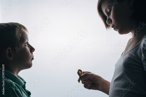 girl with a golden ribbon in her hand gives her younger brother Canvas Print