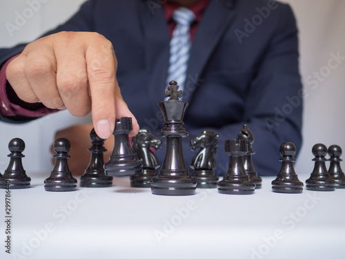 Keuken foto achterwand Rood, zwart, wit Businessman hand moving chess piece with white background, challenges planning business strategy to success concept