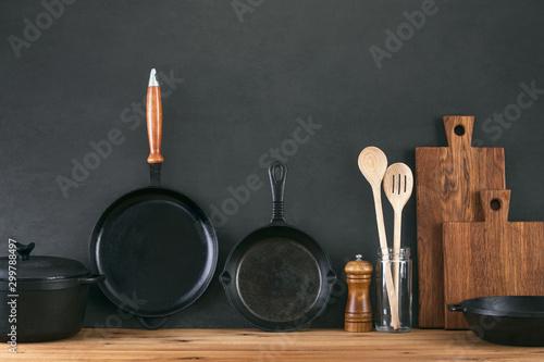 Fotografía Kitchen utensils dark background with cast iron black kitchenware