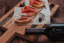 Red Wine Bottle And Rosciutto With Bread And Fresh Olives On Backing Paper. Cured Meat Served  On Wooden Board. Top View
