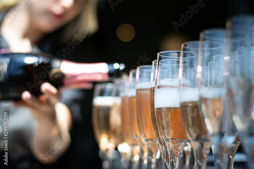 Stampa su Tela  Woman pouring champagne into glasses