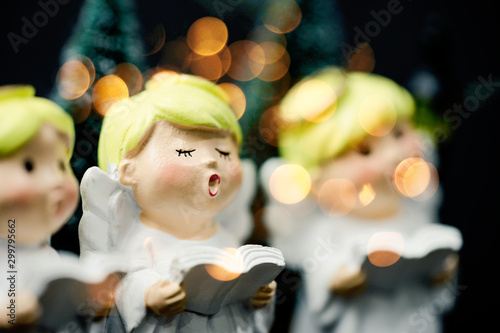 Christmas caroling or Carolers singing outside with snows.Angel group singing carol song on celebration of christmas day in winter time. - 299795662