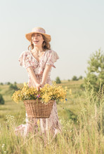 Girl With A Basket Of Flowers And A Straw Hat In A Summer Field