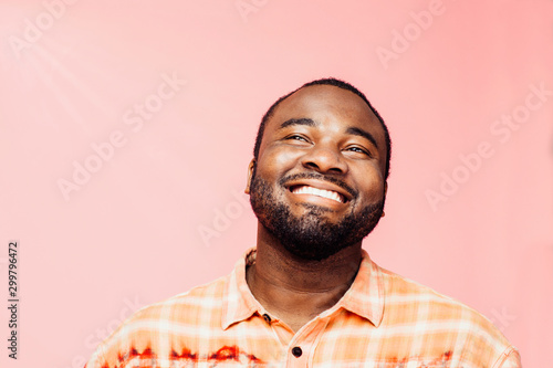 Canvas Print Portrait of a young man with big smile looking up, isolated on colorful backgrou