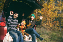 Happy Family Resting After Day Spending Outdoor In Autumn Park. Father, Mother And Child Sitting Inside Car Trunk, Smiling And Looking To The Camera. Travel In Fall Season.