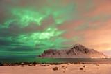 The Northern Lights (Aurora borealis) with mountain range in winter, Reine, Lofoten Islands, Nordland, Arctic