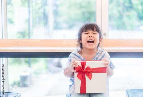 Obraz Little asian girl smile and excited and holding red gift box at home.child holding gift box in Christmas and New year concept. - fototapety do salonu