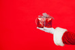 canvas print picture - Photo of Santa Claus gloved hand with giftbox, on a red background. Christmas