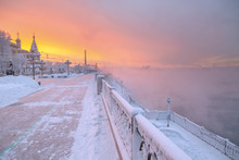 Winter Beautiful Sunset And Mist Above The Water Of River. Frosty Weather, Trees Are Covered With Fluffy Hoarfrost - Urban Winter Landscape In Siberia, Russia