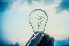 A Man Holds A Light Bulb In Hi...