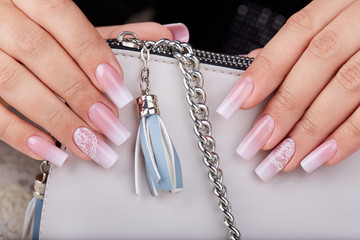 Hands with long artificial manicured nails with ombre gradient design in pink and white colors