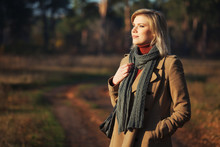 Young Fashion Blonde Woman In Beige Coat And Gray Scarf Walking Outdoor
