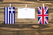 canvas print picture Hanging flags of Greece and United Kingdom attached to rope with clothes pins with copy space on white note paper on wooden background.Diplomatic relations between countries.