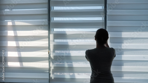 Fotomural  Woman is opening blinds in the morning in her modern apartment, copy space