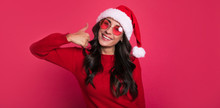 Cool Christmas. Beautiful Young Girl In Warm Outfit, Red Glasses And Christmas Hat Is Looking At The Camera, Smiling And Showing Thumbs Up With Her Right Hand.