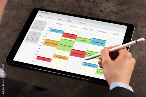 Obraz Business woman schedule her weekly program on tablet - fototapety do salonu