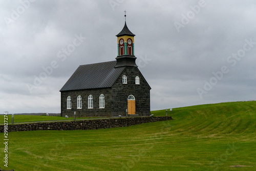 Black and colorful stone church on a hill