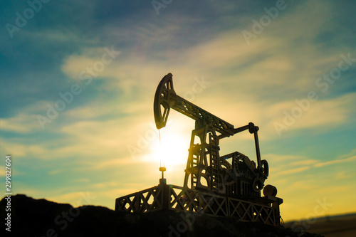 Obraz Oil pump on a sunset background. Oil production, fuel, natural resources. - fototapety do salonu