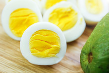 Boiled Eggs With Avocado On A Wooden Board.