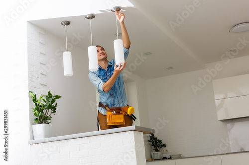 Obraz Electrician is installing and connecting a lamp to a ceiling. - fototapety do salonu