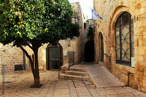 Orange tree on the street in the center of the old city of Jerusalem. The street is Jerusalem.