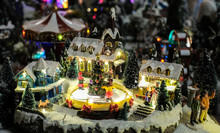 Christmas Time, Miniature Of Houses And People, Winter And Snow At Night, Xmas Houses Decorated With Lights