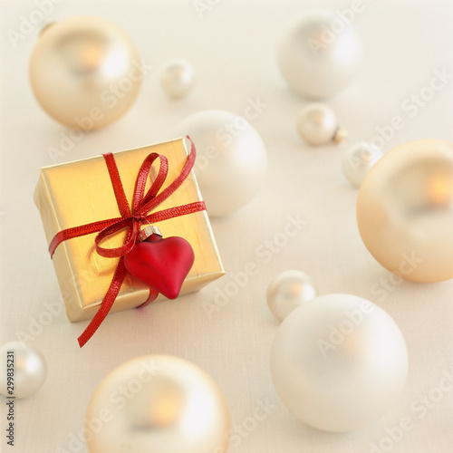 Close-up of romantic Christmas gift present with gold wrapping paper and red heart decoration surrounded by Christmas ornaments on white background. Selective focus on gift.
