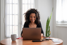 Shot Of Young Latin Woman Working At Home With Laptop And Documents