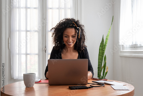 Photographie Shot of young latin woman working at home with laptop and documents