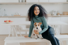 Joyful Afro Woman Sits At White Bench Together With Dog Against Kitchen Interior, Table With Plate Full Of Red Apples, Get Pleasure While Playing At Home. Animal Owner Feels Care And Responsibility