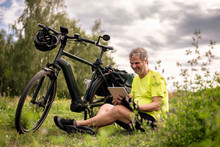 Mature, Man Using Digital Tablet During His Bike Tour With An E-bike