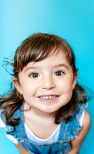 Portrait Of Cute Little Girl Smiling Very Expressive On Blue Background