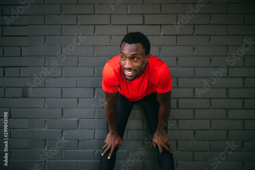 Smiling young sportive man taking a break from workout in front of a brick wall - 299843098