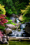 Waterfall long exposure vertical view with maple trees in Kyoto Japanese green Garden in Holland Park green summer zen lake pond water in London, UK