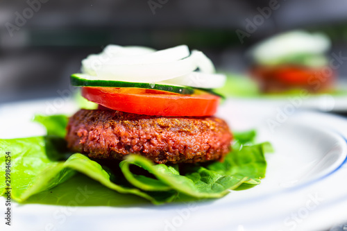 Fotografiet Macro side closeup of vegan meat sausage patty on plate with romaine lettuce lea