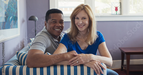 Fotografía Portrait of senior multi ethnic couple sitting on couch smiling at camera